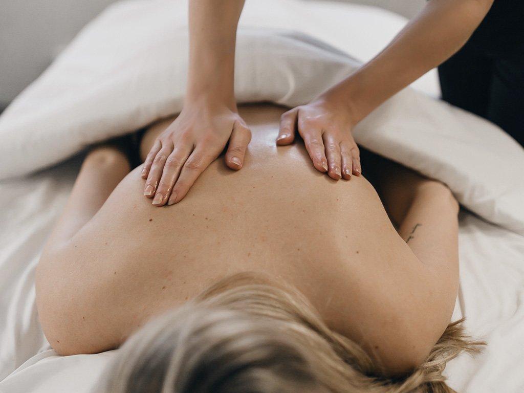 Une femmes recevant un massage dans l'une des chambres de l'Auberge du Vieux-Port.